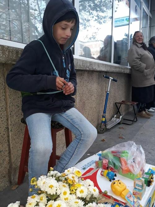 Un copil de 10 ani își vinde jucăriile pe o stradă din Mioveni