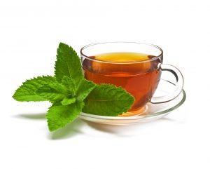 Ceai de mentă în ceașcă, alături de câteva frunze de mentă