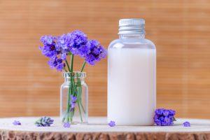 Ulei de lavandă - Flori de lavandă în vază alături de un recipient cu lotiune