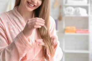 Vitamina A pentru par- femeie cu parul lung in halat de baie care pune vitamina pe lungimea părului